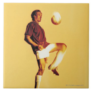 soccer player bouncing ball off knee large square tile