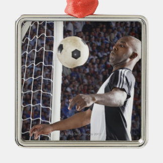 Soccer player facing mid air ball in goal mouth christmas ornament