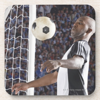 Soccer player facing mid air ball in goal mouth coaster