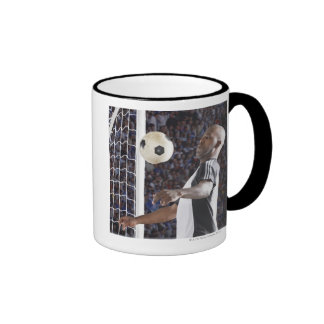 Soccer player facing mid air ball in goal mouth mugs