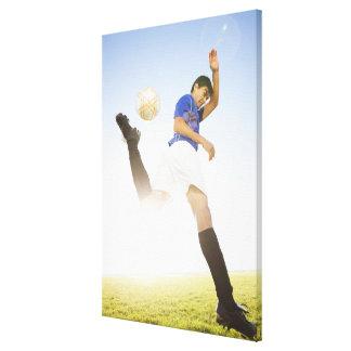 Soccer player jump kicking canvas print
