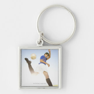 Soccer player jump kicking key ring