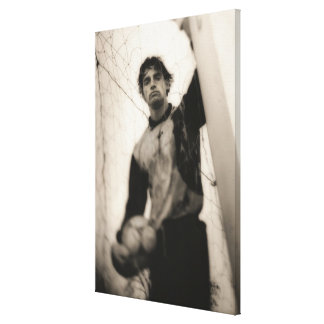 Soccer player standing behind net canvas print