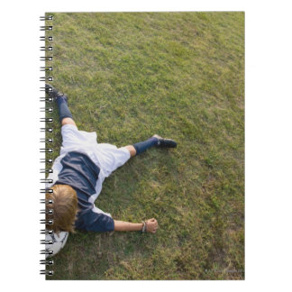 Soccer player with head on football spiral notebook