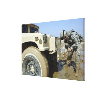 Soldier unties a rope to tow a humvee canvas print