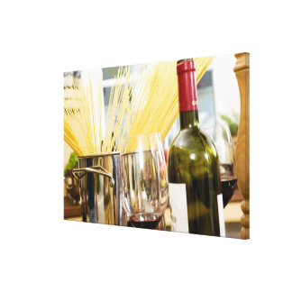 Spaghetti in pan with wine bottle and glasses canvas print