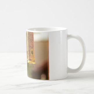 Sparrow eating coffee mug