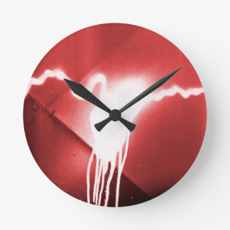 Sprayed graffiti on red metal round clock