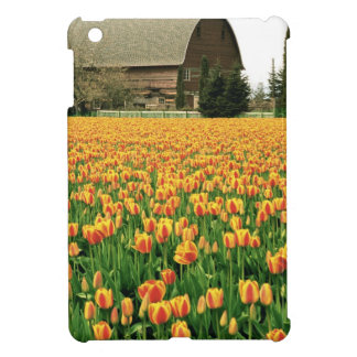 Spring tulips bloom in front of old barn. case for the iPad mini