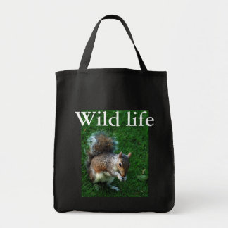 squirrel eating a nut tote bags