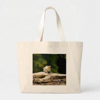 Squirrel on log tote bag