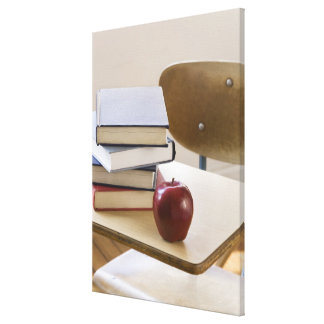 Stack of books, apple, and school desk canvas print