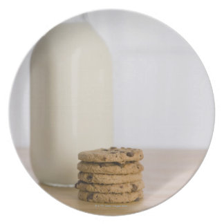Stack of chocolate chip cookies milk in a glass plate