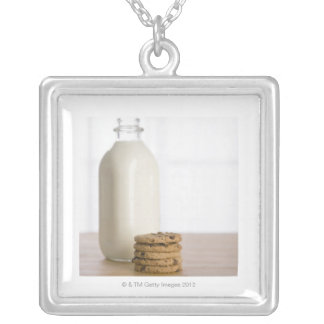 Stack of chocolate chip cookies milk in a glass silver plated necklace