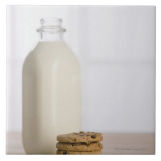 Stack of chocolate chip cookies milk in a glass tile