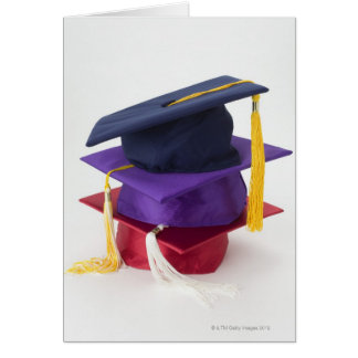 Stack of graduation mortarboards greeting card