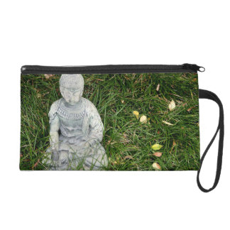 statue on leaf covered lawn wristlet purse