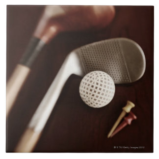 Still life if vintage golf clubs, tees and ball. tile