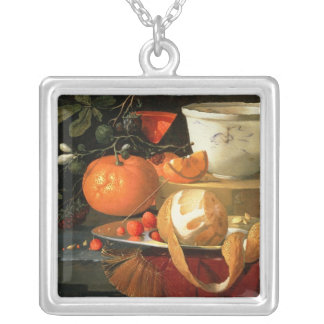 Still life of an orange silver plated necklace