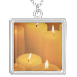 Still life of lighted candles silver plated necklace