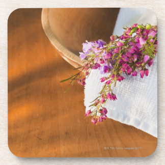 Still life with purple flowers, towel and wooden coaster