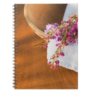 Still life with purple flowers, towel and wooden spiral notebook