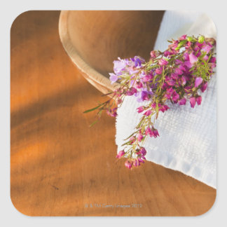 Still life with purple flowers, towel and wooden square sticker