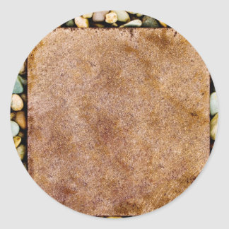 Stone slab surrounded by grungy pebbles round sticker