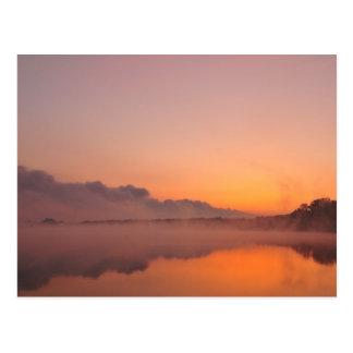 Stormfront coming, orange sunrise at lake postcard