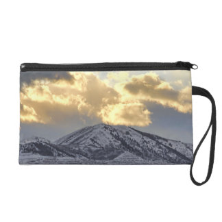 Stormy Sunset Over Snow Capped Mountains Wristlet Clutches