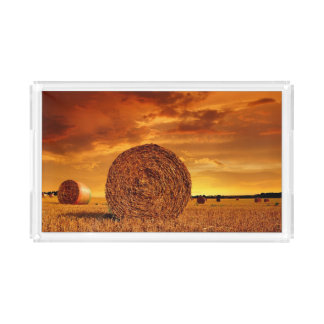 Straw bales on farmland with red cloudy sky acrylic tray