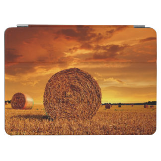 Straw bales on farmland with red cloudy sky iPad air cover