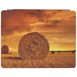 Straw bales on farmland with red cloudy sky iPad cover