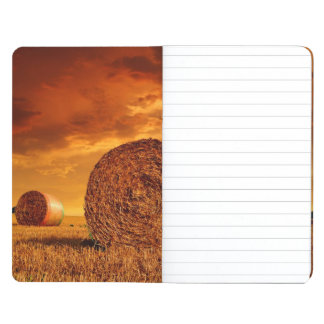 Straw bales on farmland with red cloudy sky journal