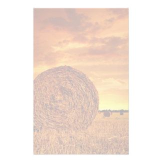 Straw bales on farmland with red cloudy sky stationery