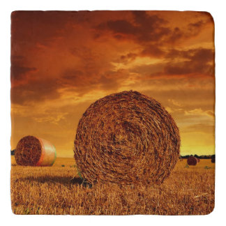 Straw bales on farmland with red cloudy sky trivet