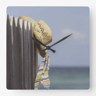 Straw Hat Hanging On Fence At Beach Wallclock
