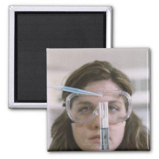 Student Holding Test Tube Square Magnet
