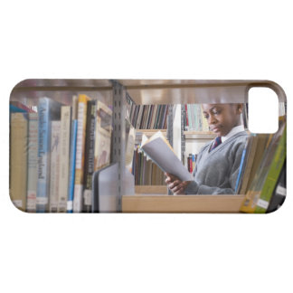 Student in school uniform looks at a book in a barely there iPhone 5 case