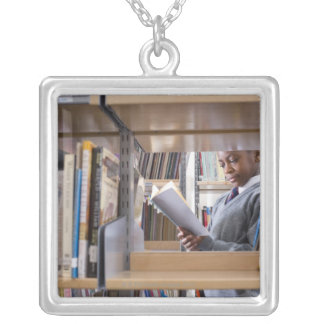 Student in school uniform looks at a book in a custom necklace