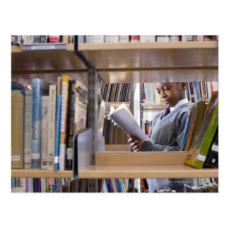 Student in school uniform looks at a book in a postcard