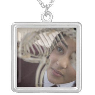 Student looking at animal skeleton silver plated necklace