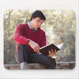 Student Reading Book and Sitting on Stone Wall Mouse Pad