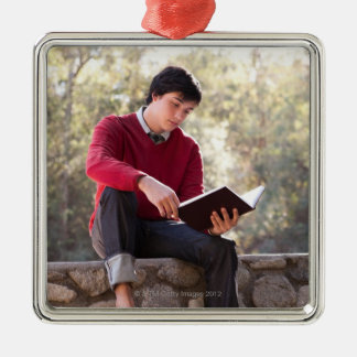 Student Reading Book and Sitting on Stone Wall Silver-Colored Square Decoration