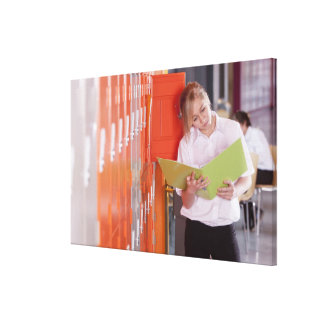 Student removing binder from school locker canvas print