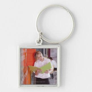 Student removing binder from school locker keychains