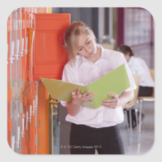 Student removing binder from school locker square sticker