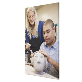 Student sculpting bust in classroom canvas print