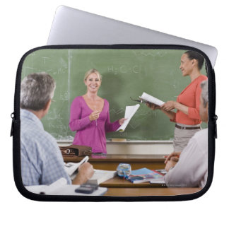 Student talking to class and standing by teacher laptop sleeve