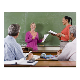 Student talking to class and standing by teacher postcard